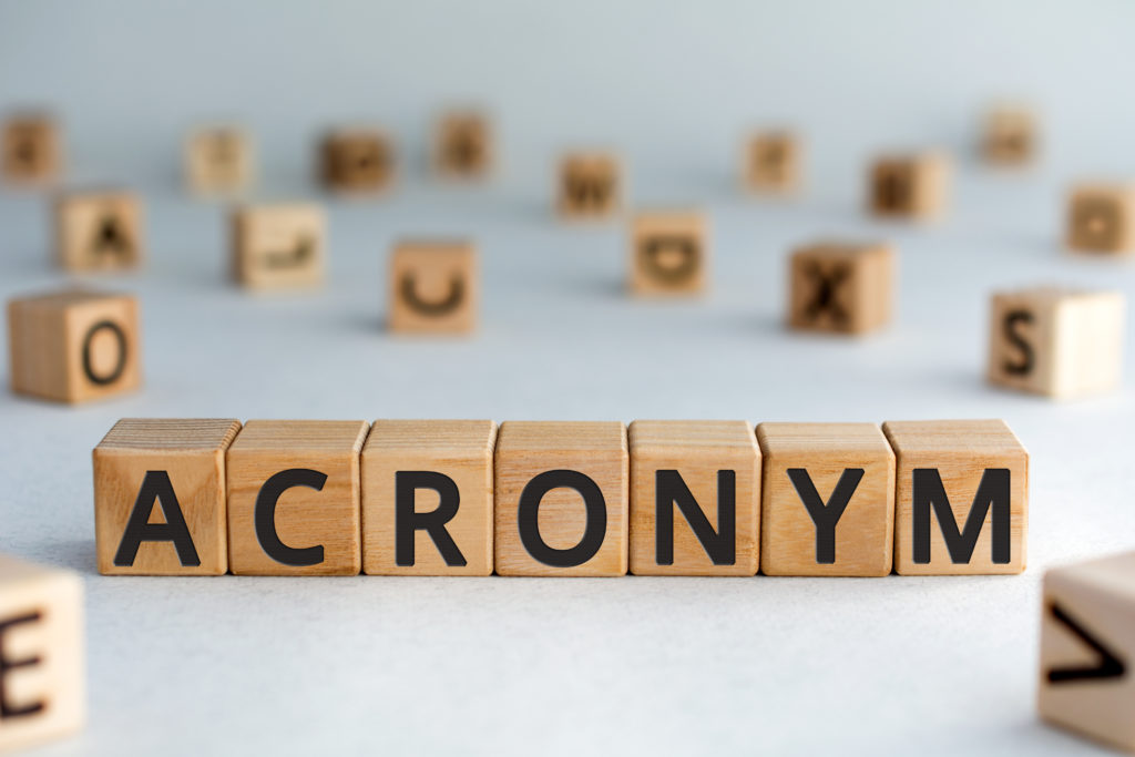 Word from wooden blocks with letters, use of acronyms in the modern world abbreviation concept, random letters around, top view on wooden background.