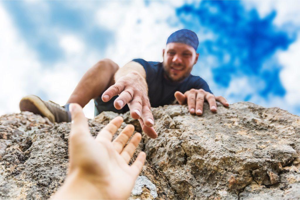 Adventurers helping each other climb a mountain.