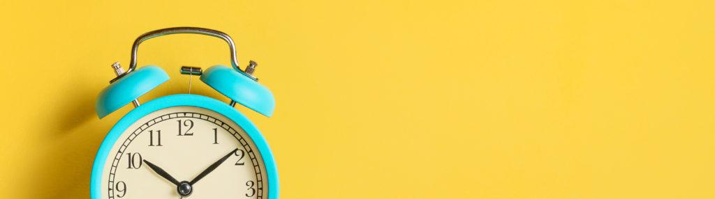 Vintage alarm clock on yellow background.