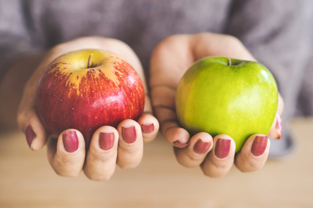 Woman hand holding red and green apple fruit for diet.