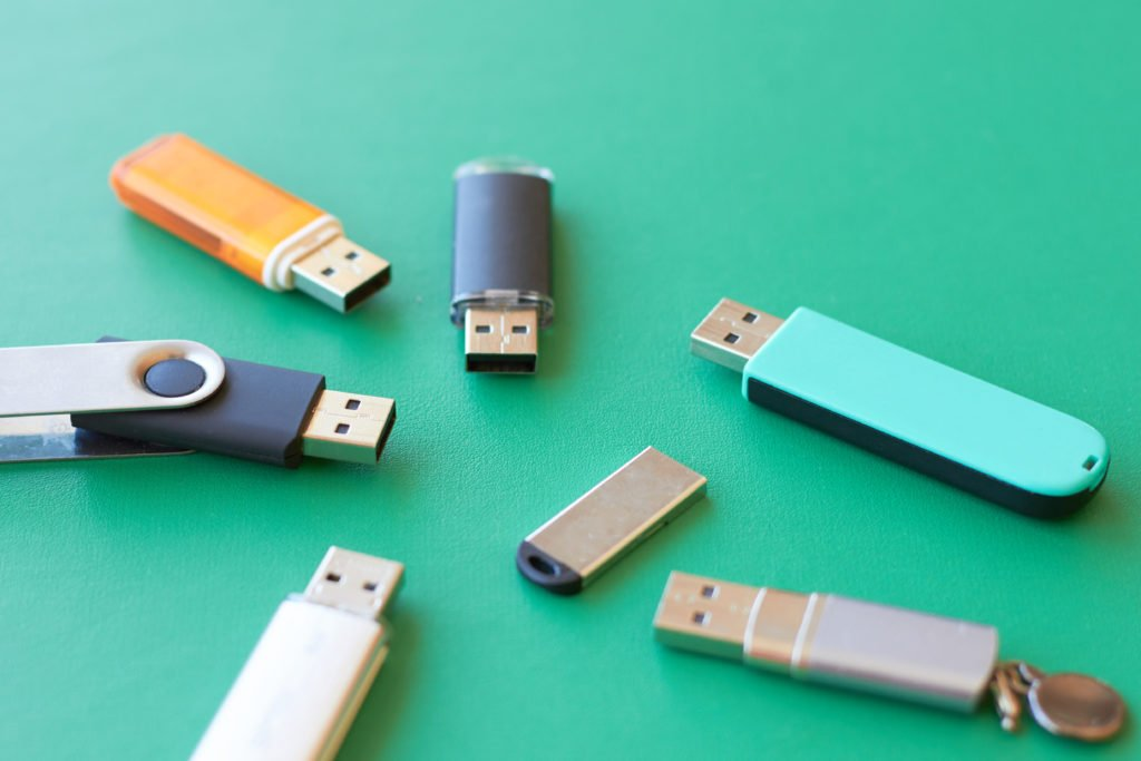 Assorted USB flash drives in green background.
