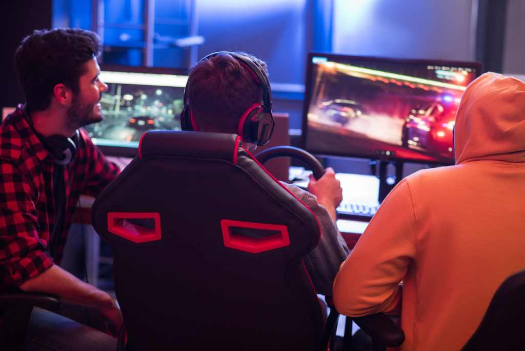 Back view of gamers playing car racing game on computer.