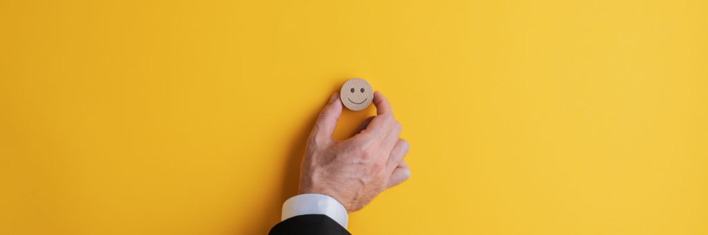 Wide view image of hand of a businessman placing a wooden cut circle with a smiling face on it over yellow background.
