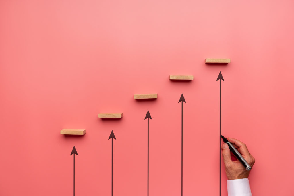 Businessman drawing upwards pointing arrows to support wooden pegs positioned in stairway like structure in a conceptual image of business growth and development.