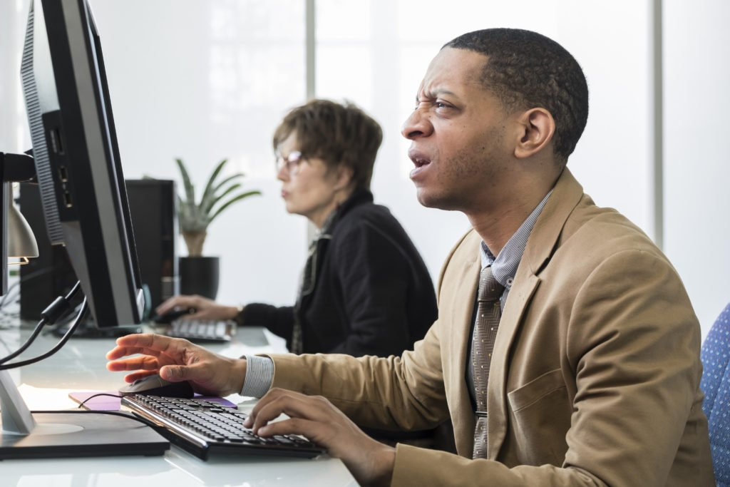 Businessman squinting his eyes and getting frustrated at the computer.