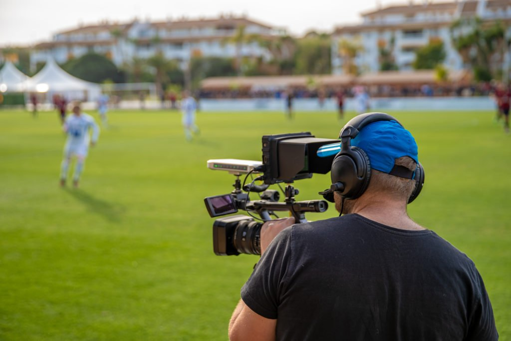 Cameraman shooting live broadcast from a soccer game.