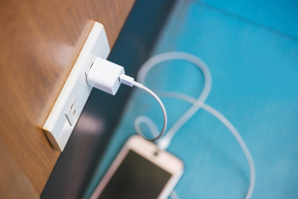 Charging smartphone in a public space, blue floor.