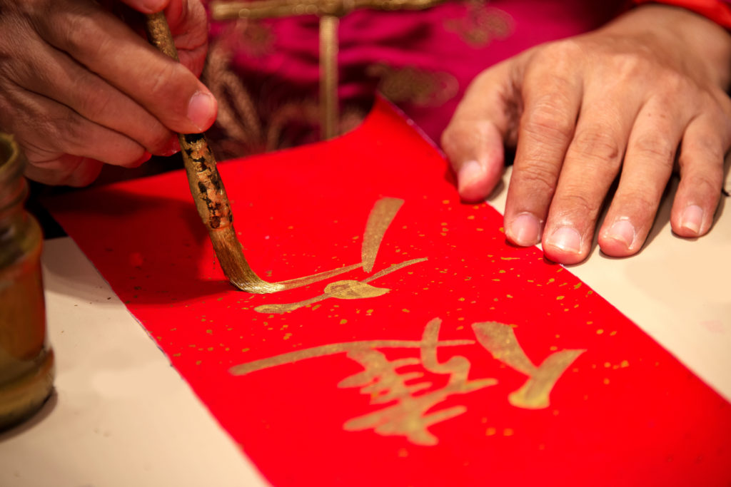 Chinese calligraphy master writing a word on red paper.