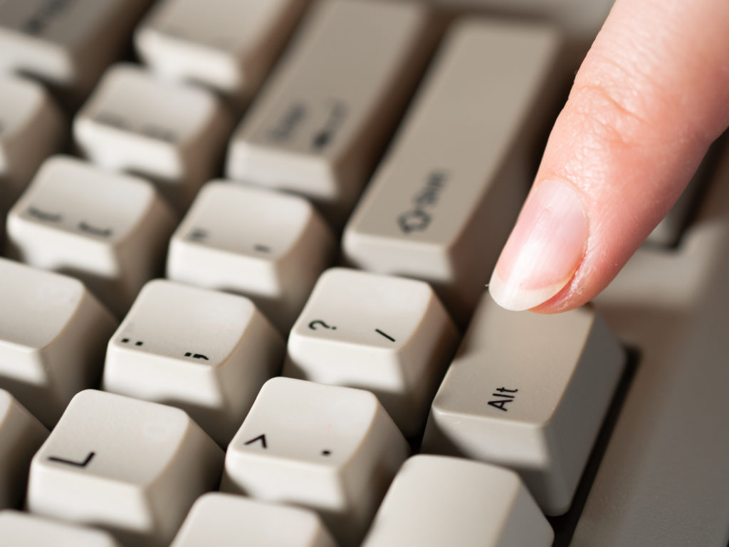 Close-up of forefinger pressing the keyboard ALT button.