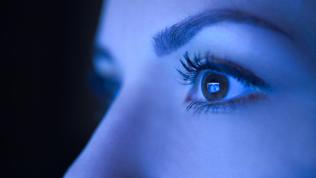 Close-up of a woman's eyes against blue light monitor.