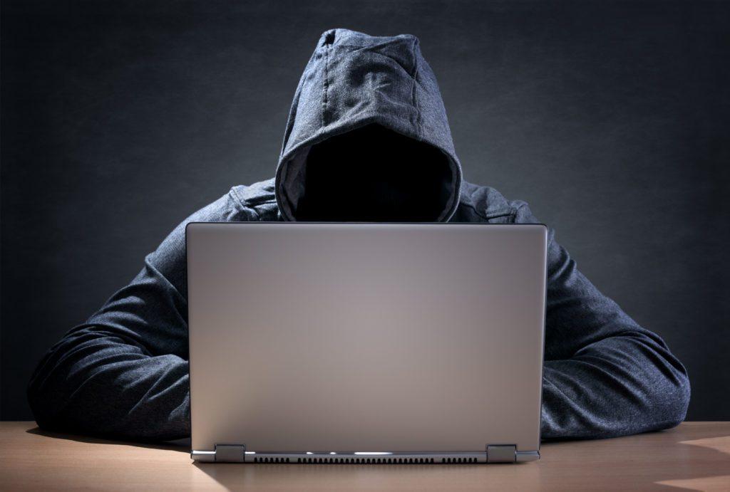Computer hacker stealing data from a laptop.
