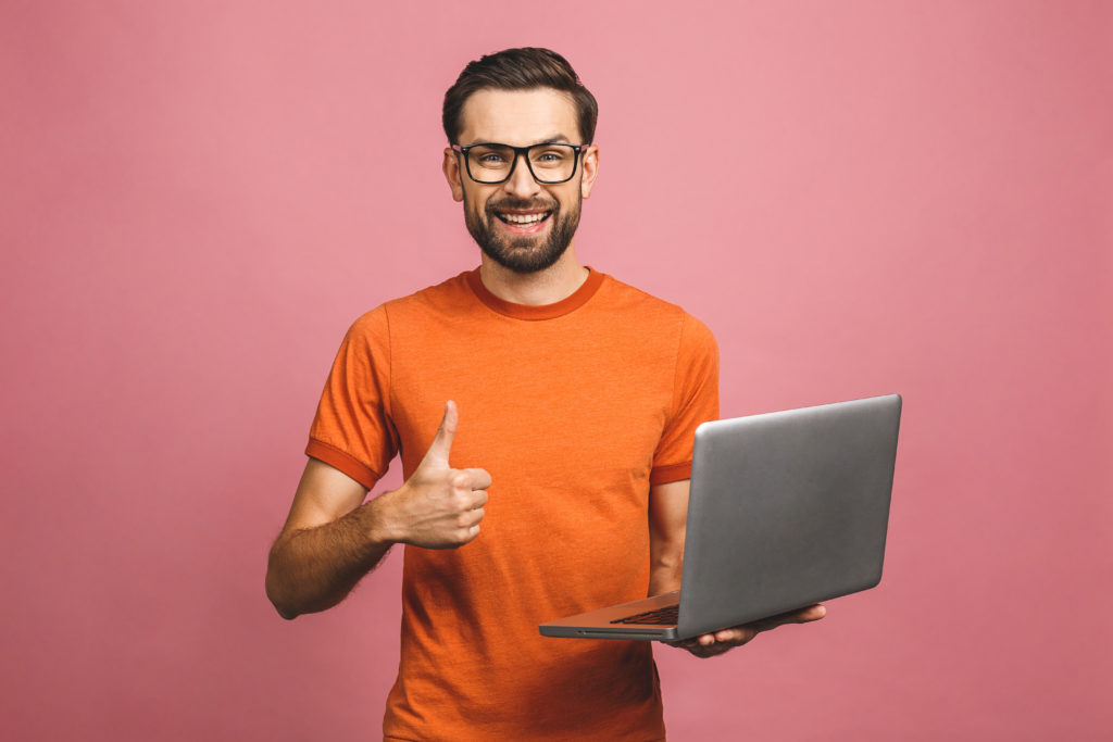 Confident man holding a laptop while doing a thumbs up pose with his hand, pink background.