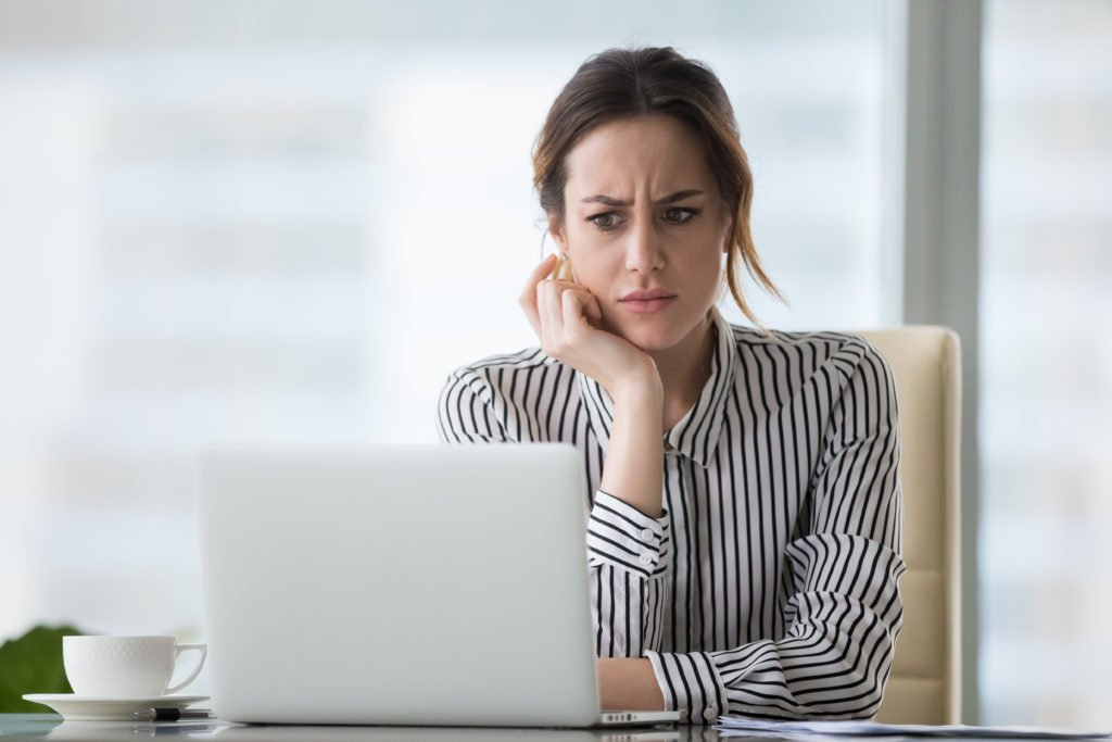 Confused businesswoman looking at a problem on her laptop.