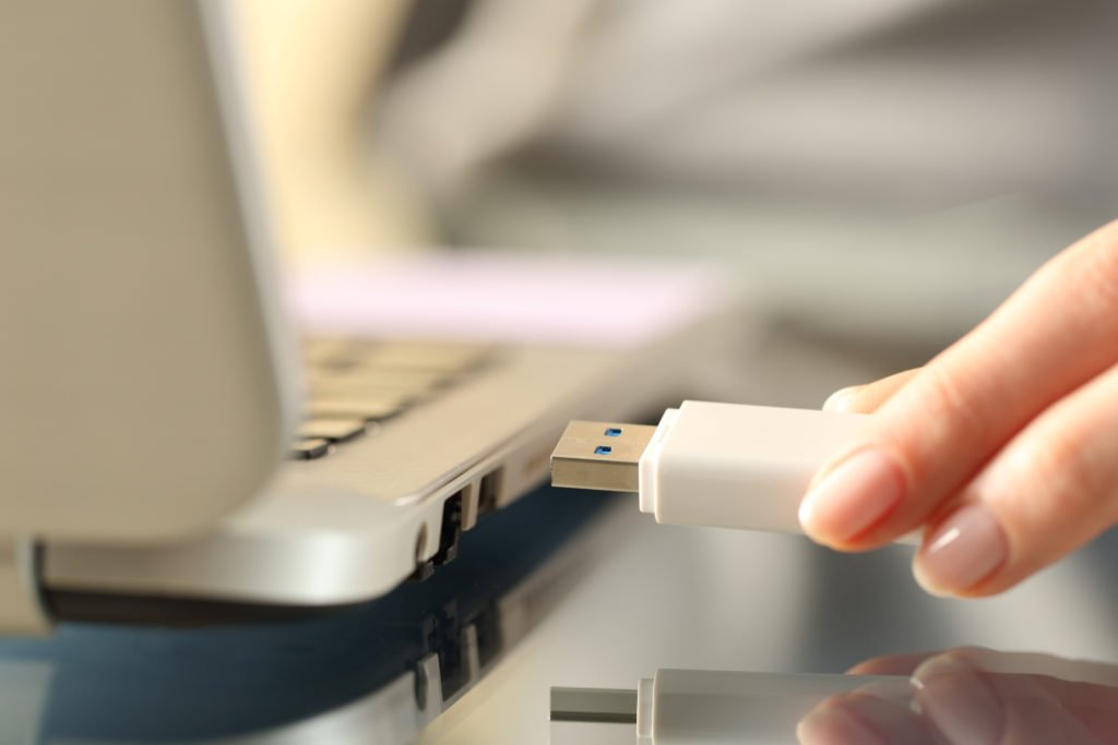 Woman connecting white USB flash drive to a laptop.
