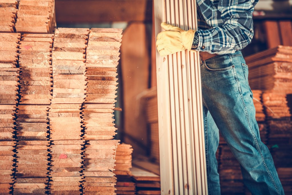 Contractor with Planks. Caucasian Carpenter with Pile of Wood Boards. Construction Materials Theme.