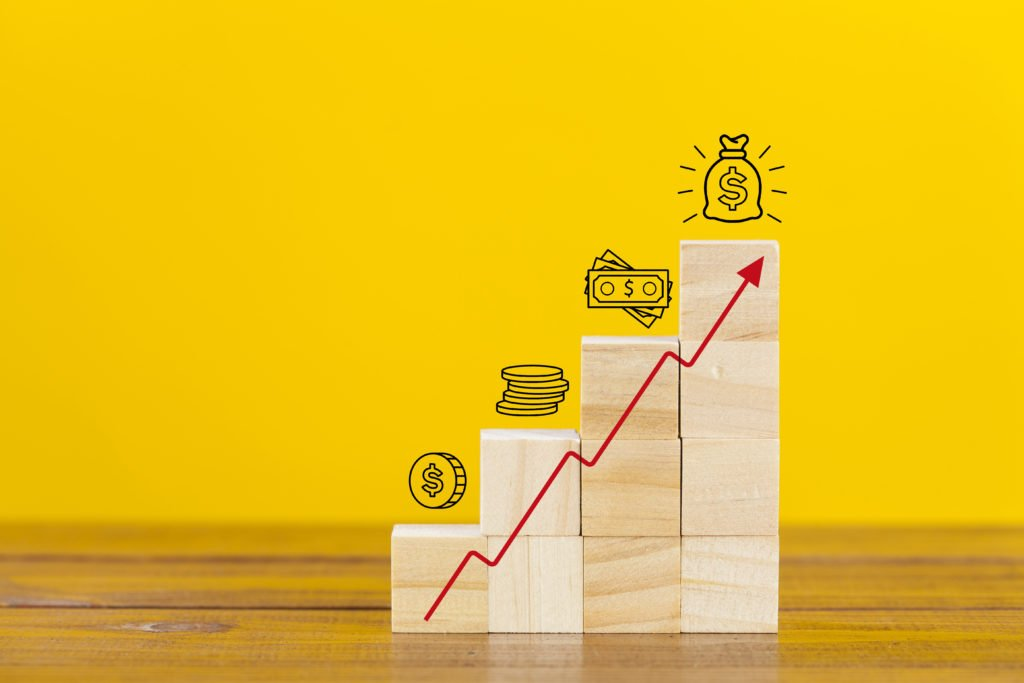 Rising earnings chart made from wooden cubes. Business growth success process.