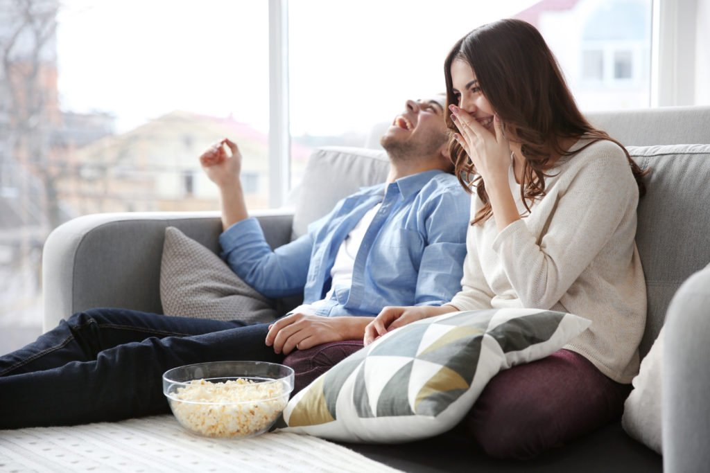 Couple watching television and having fun with popcorn.