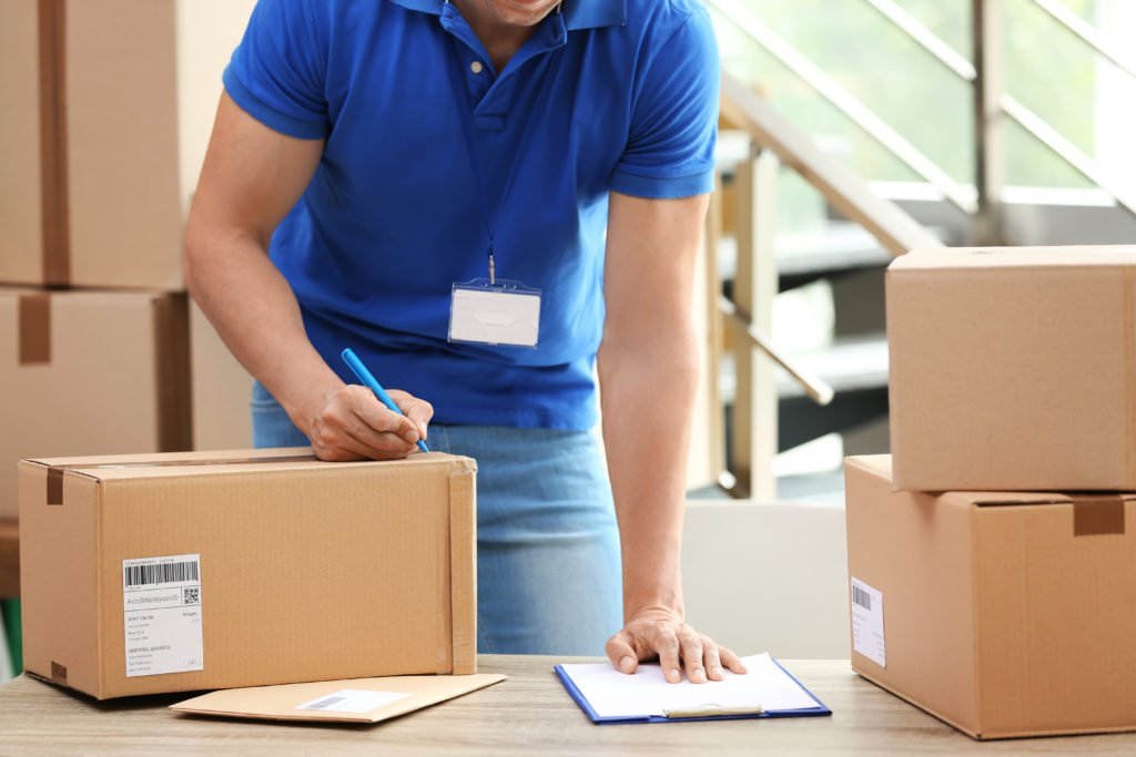 Courier staff taking notes on parcel for delivery.