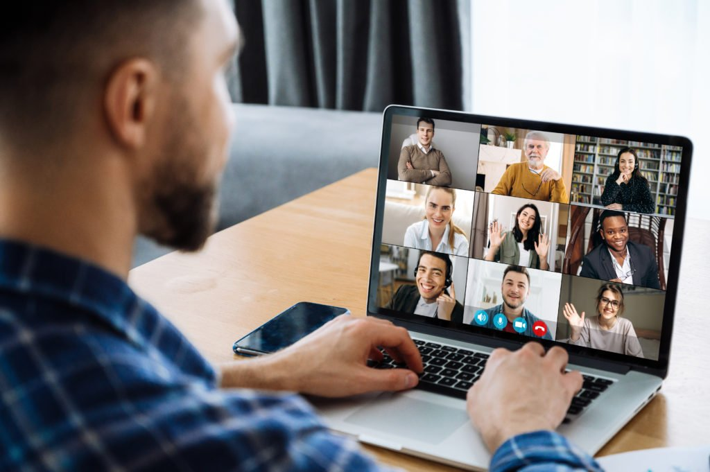 Man using laptop while having an online meeting with coworkers.