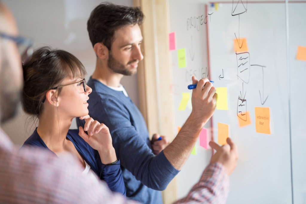 Creative people brainstorming and writing on a transparent board.