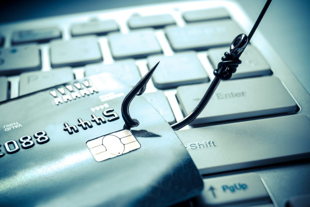 Credit card on a keyboard getting caught by fish hook.
