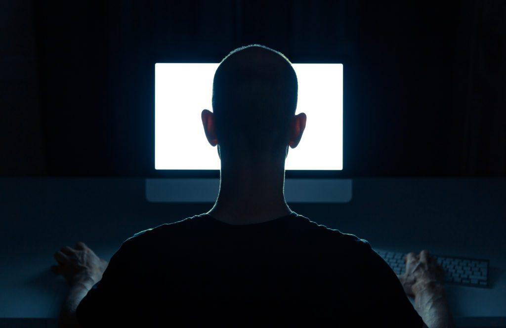 Man with criminal intentions using desktop computer.