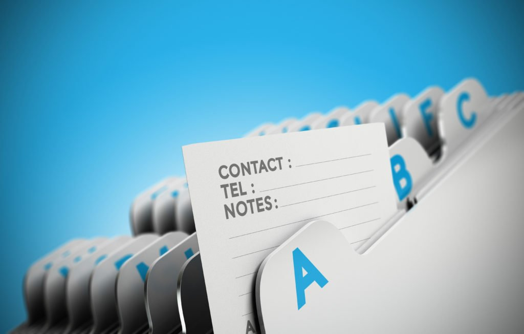 Folder tab organized alphabetically with focus on a contact note, blue background. Conceptual business image for illustration of customer file, client data management or address list.