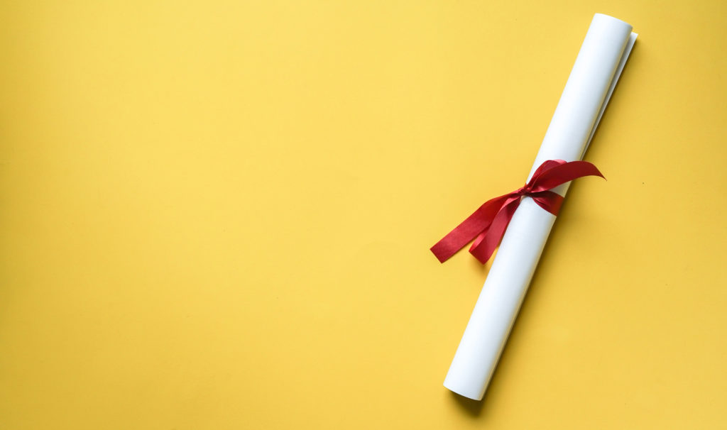 Close up top view of certificated degree on yellow background for education concept.