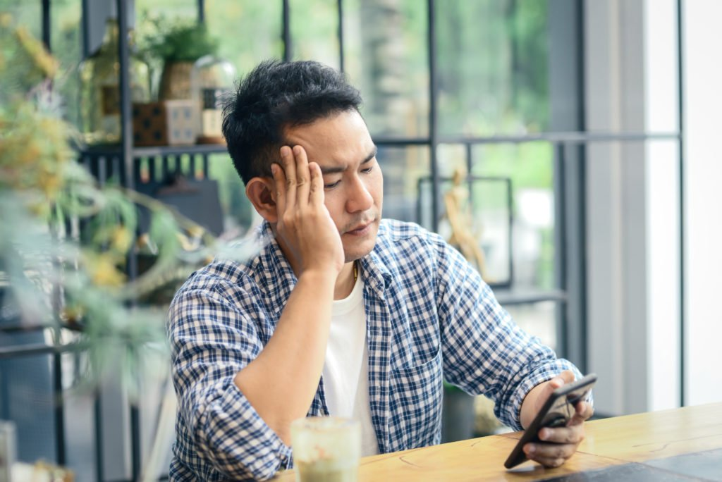 Disappointed and stressed man looking at his phone while inside a cafe.