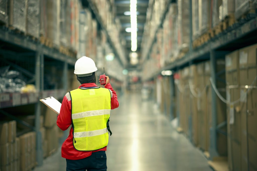 Male manager using handheld in a large warehouse worker checking delivering boxes.