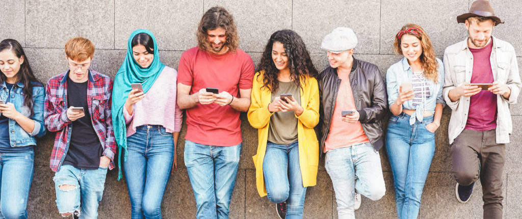 Group of diverse friends social networking on mobile phones.