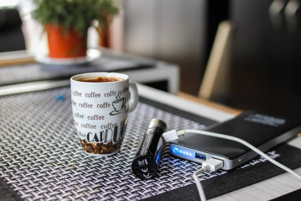 E-cigarette connected to a powerbank beside a cup of coffee.