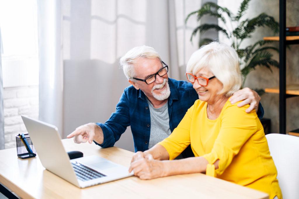 Cheerful elderly couple enjoys using the laptop.
