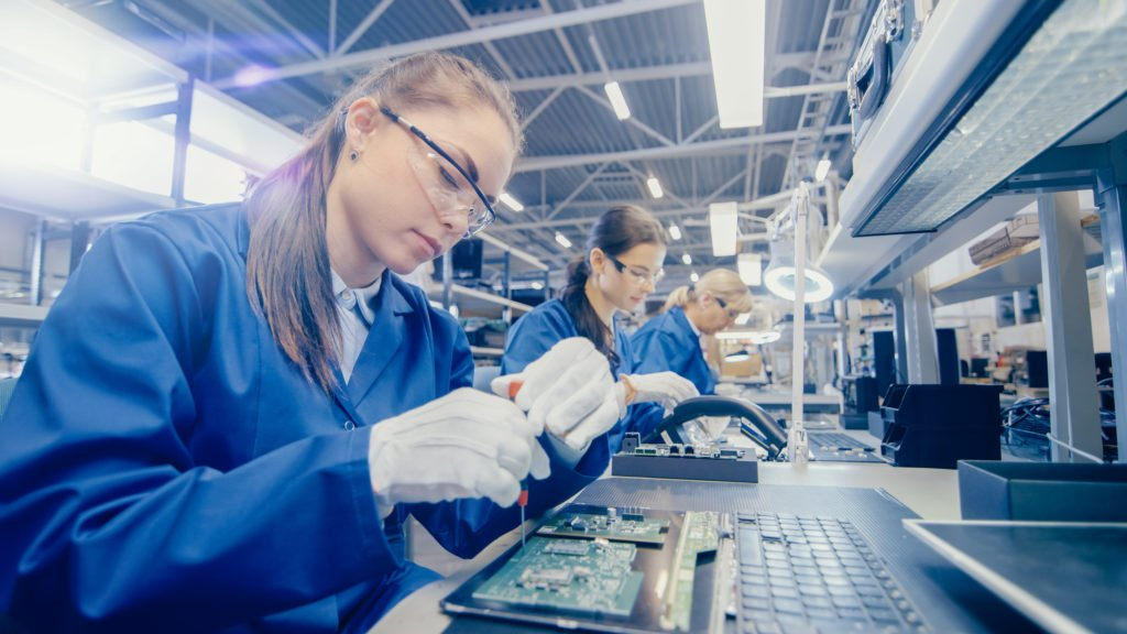 Female Electronics Factory Worker in Blue Work Coat and Protective Glasses is Assembling Laptop's Motherboard with a Screwdriver. High Tech Factory Facility with Multiple Employees.