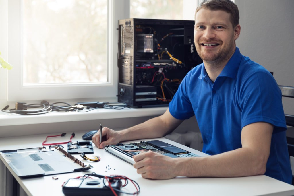 Electronics technician smiling while at work.