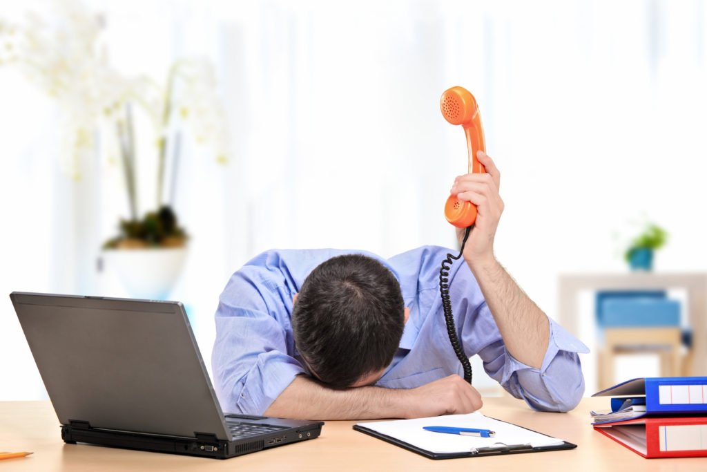 Exhausted employee holding a telephone in his office.
