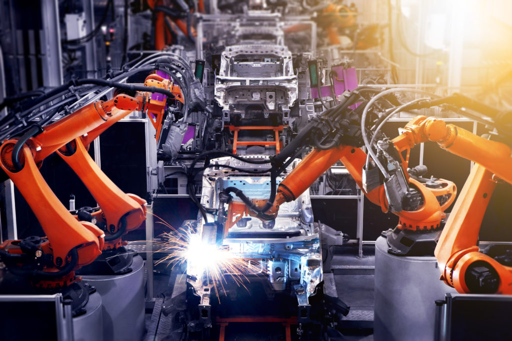 The factory floor of automobile production is producing cars.