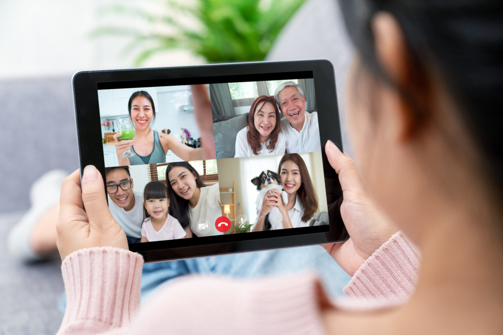 Girl using tablet while having a video call with family.