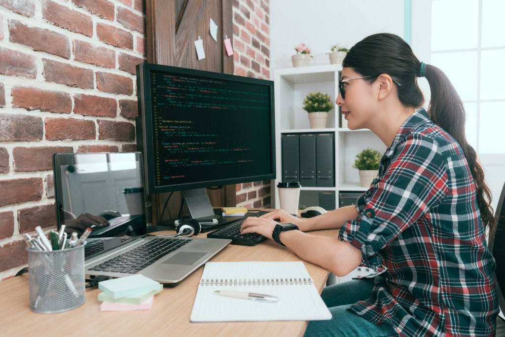 Female programmer smiling while coding on the computer.