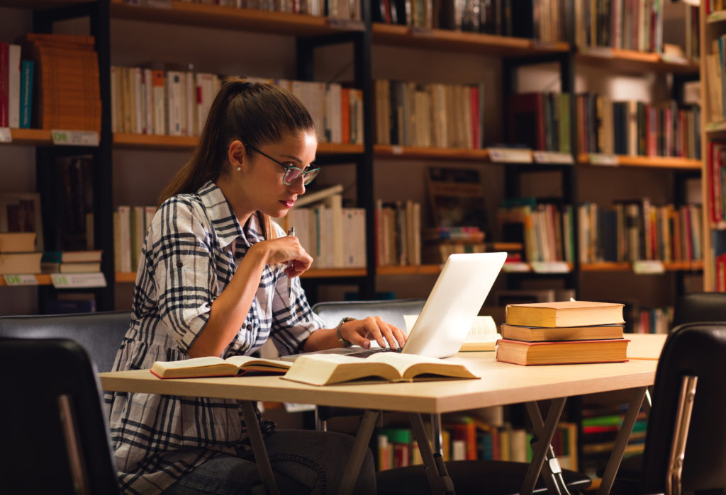Female student studying inside a library with her laptop.