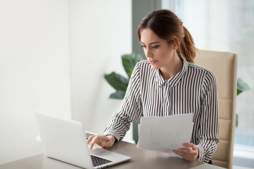 Focused businesswoman typing on her laptop while holding papers.