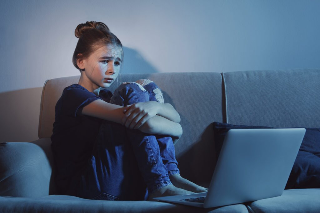 Frightened girl looking at a laptop inside a dark room.