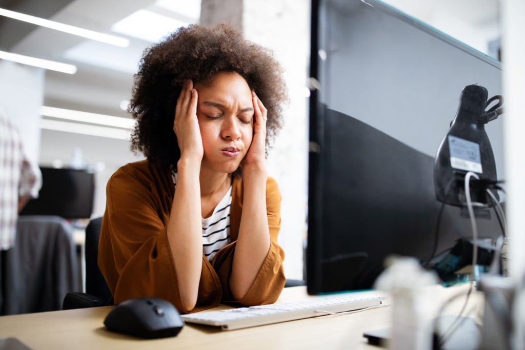 Frustrated woman in front of a computer inside the office.