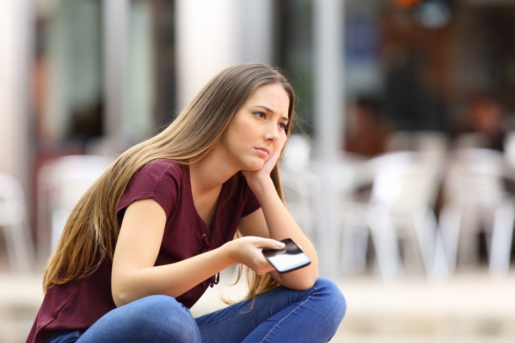 Girl waiting for a phone call in a public place.