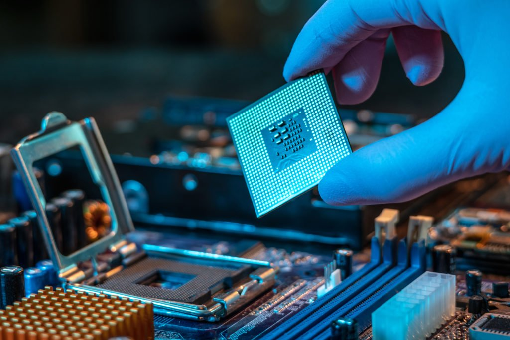 Engineer's gloved hand holding the CPU chip with motherboard on the background.