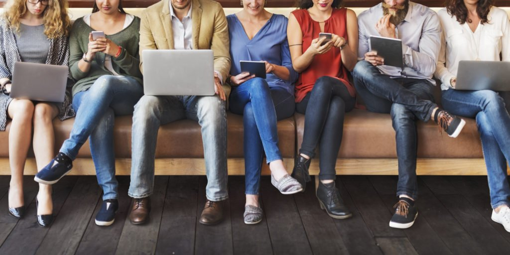 Group of people using different digital devices.