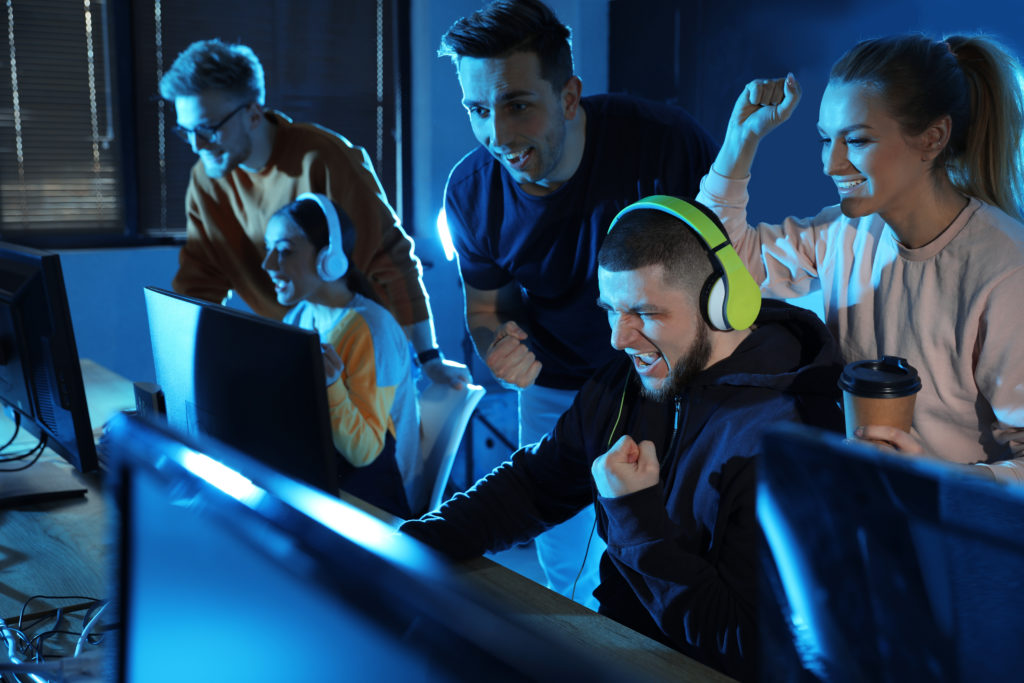 Group of excited people playing games in internet cafe.