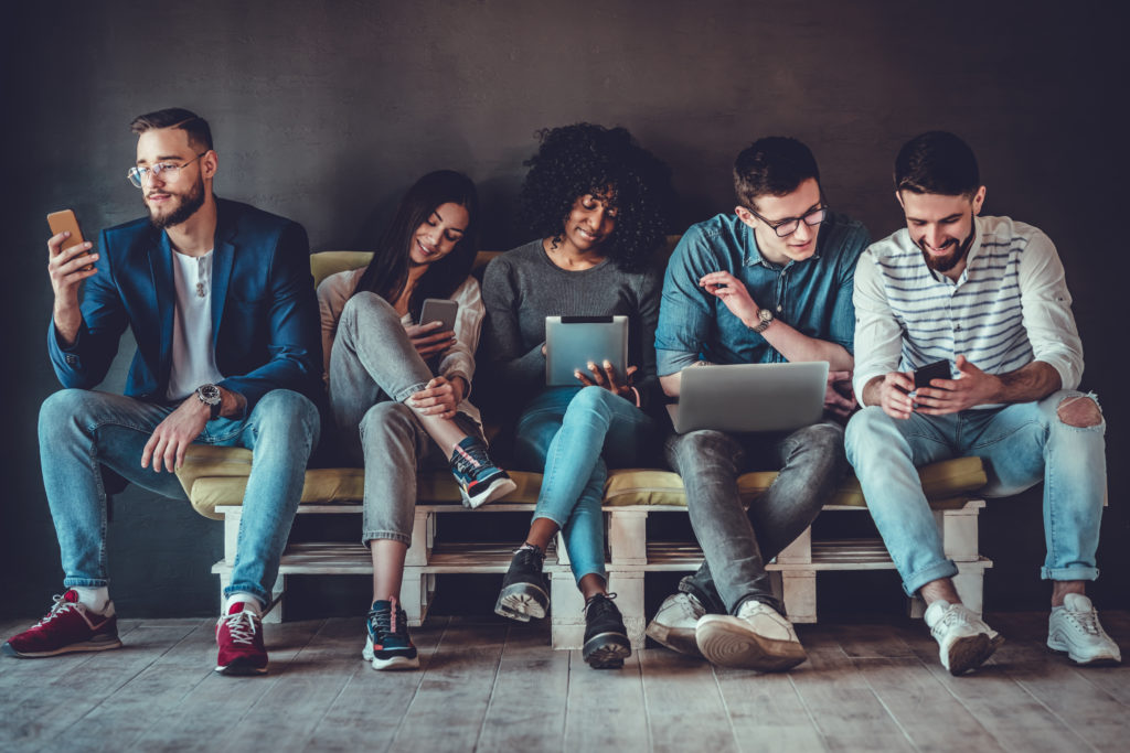 Group of happy people sitting on sofa and using digital devices.