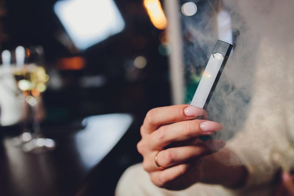 Hand holding a gray e-cigarette.