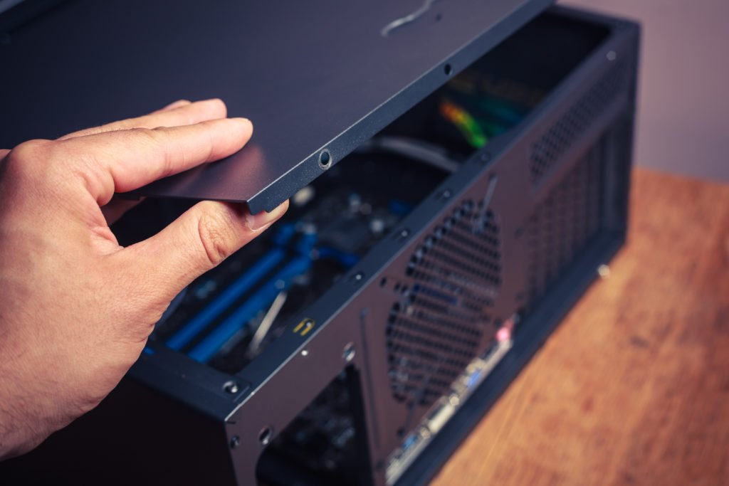 Hand opening a computer case.